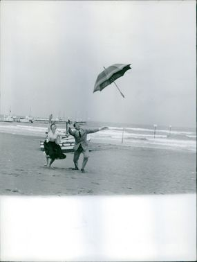 Man and woman at beach, enjoying and trying to catch the umbrella.