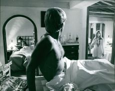 Sven-Bertil Taube sitting up in bed looking at Jane Asher, on set of The Buttercup Chain.