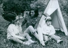 A photo of an Italian-born actress who first became famous as the twin sister of film star Pier Angeli (Anna Maria Pierangeli) Marisa Pavan enjoying picnic outdoor with the young boys sitting on the grass.