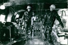 Workers carrying a heavy part of machine.