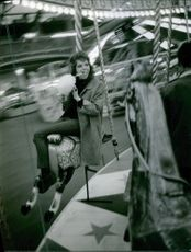 Rita Tushingham eating a cotton candy while riding the merry go round.