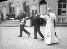 Pope Paul VI walking along with other people.
