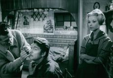 Jill Haworth standing behind a man  who is sitting and have someone fix something on his face.