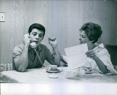Frankie Avalon is talking to someone on the phone, his wife Kathryn Diebel sitting beside of him and enjoying his speech with smiling face
