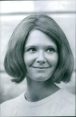 A close up photo of a girl, with short hair. smiling.