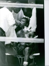 Sugar Ray Robinson is given first aid during a boxing match.  Year: 1962