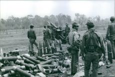 Soldiers standing and guarding the weapons lying on the ground. 1970.