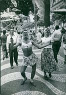 Two men wearing women's clothes and dancing on the street.
