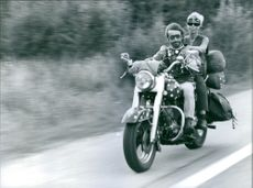 A vintage photo of a man and a woman travelling to other place riding a vintage Harley Davidson motorbike.