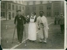 A nun and caretaker walking with two handicapped person, 1915.