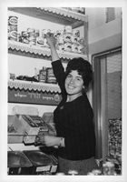 Woman in the shop while smiling.