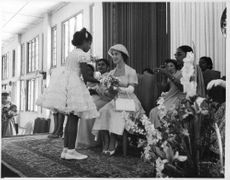 Princess Margaret being greeted by a little girl, on stage.