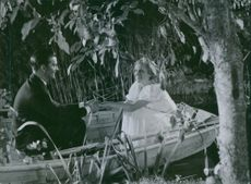 A scene   from the film The family secret. Ingrid Borthen and Kotti Chave sitting in a boat. 1936