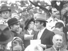 Aga Khan IV surrounded by people and talking to man.