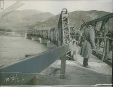 Soldiers passing by the bridge, while carrying luggage. 1913