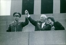 A photo of Russian leader Nikita Khrushchev (1894 - 1971) holds up the hands of Valery Bykovsky who holds the record for time in space, and  Valentina Tereshkova, the first woman in space, as Moscow welcomes the cosmonauts in Red Square.