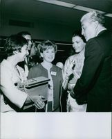 Elizabeth Allen with other people listening song from Cesar Romero.