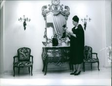 Renata Tebaldi reading letter in front of mirror.