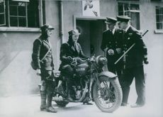 Female motorcycler arrive at one of the British marines signal stations and report to Rear Admiral C.S. Holland, director of the British Navy.