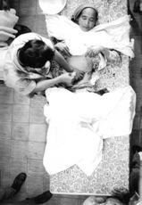 A medical professional performing wound care to the patient. 1968