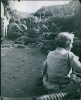 A group of military men sitting in a corner on a piled rocks in North Korea, 1950.