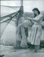 Vintage photo of a lady weaving a fishing net in Sisters of Nazareth. Photo taken on December 10, 1963.