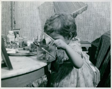 A child playing the adult cosmetic materials
