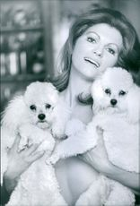 Rosanna Yanni holding two furry dogs each in her hands covering her body.