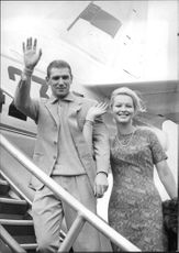 Marina Vlady and her husband Robert Hossein waving hat airport.