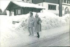 Michele Morgan walking with a woman, on snow.