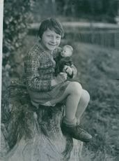 Orphaned girl, Tania Joel, holding a doll, arrived in England from Belsen.