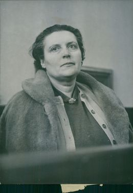 A woman wearing a coat and looking from afar.