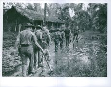 Soldiers passing through a flooded area in Vietnam.
