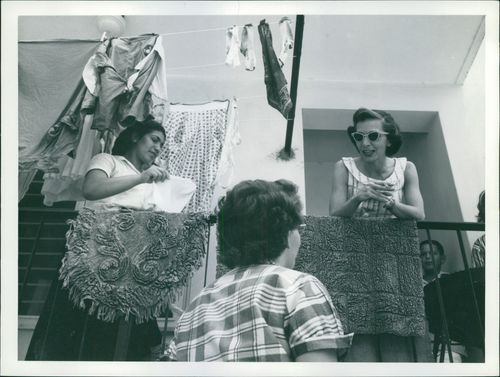Women having conversation while hanging the wet clothes.