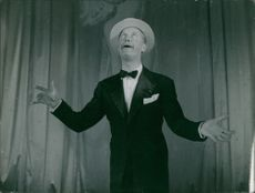 Maurice Chevalier performing on stage.