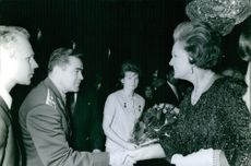 Valentina Tereshkova on the background of a man and a woman, shaking hands. 1965