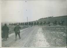 Soldiers riding a horses in the field during World War I.