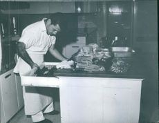 A chef is preparing dish inside the kitchen. 1946