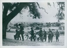 Soldiers approaching underneath under tree.