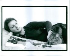 Woman pampering cat and smiling.