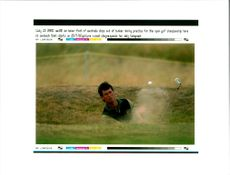 Golfer Ian Baker-Finch chips out of bunker during practice
