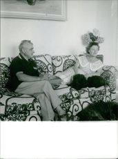 Man and woman relaxing on couch.