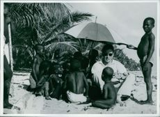 A man sitting on sand with children.1962