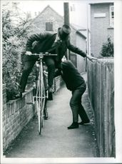 One foot on the brick wall, one hand on the fence and somebody to hold the bicycle steady.