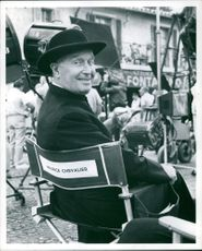 Maurice Auguste Chevalier sitting at a shooting location.