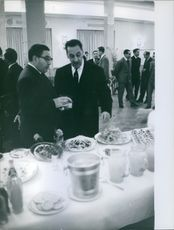 Former Algerian President  Ferhat Abbas having a conversation with a man in front of a dining table