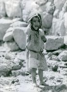 Child crying on a rocky field in Yemen.