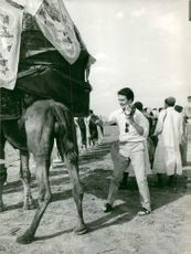 Jacques Charrier standing beside horse.