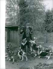A man holding a chicken, surrounded by dogs. December 18, 1962.