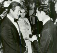 "Roger Moore and his wife Luisa in talks with Prince Charles at the premiere of the James Bond movie ""Deadly Point of View"" at the Odeon Theater"